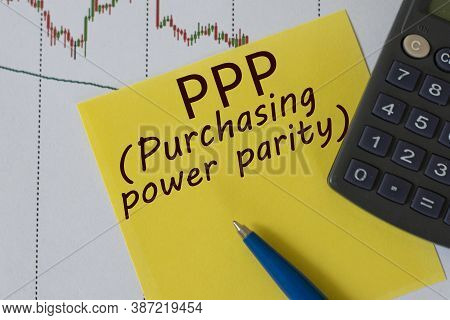 Ppp (purchasing Power Parity) Words On Yellow Sheet On Table With Pen, Calculator And Graph. Busines