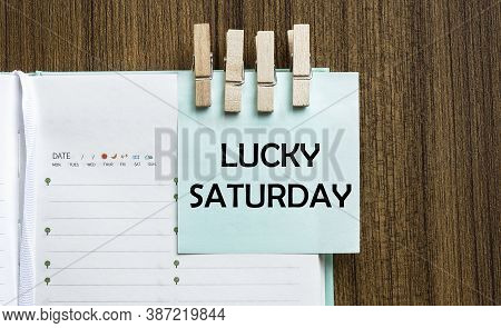 Lucky Saturday Notes Paper And A Clothes Pegs On Wooden Background