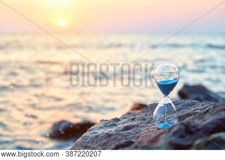 Sunset Over Sea And Nature Landscape. Hourglass With Sand Standing On Rock. Running Of Time And Rela