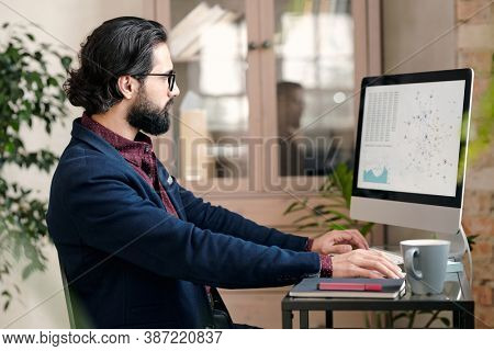 Serious young broker or economist in formalwear sitting by table in front of computer monitor and studying financial data and graph on screen