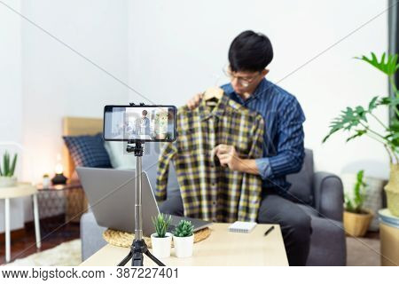 Young Asian Male Blogger Recording Vlog Video On Camera Review Of Product At Home Office, Focus On T