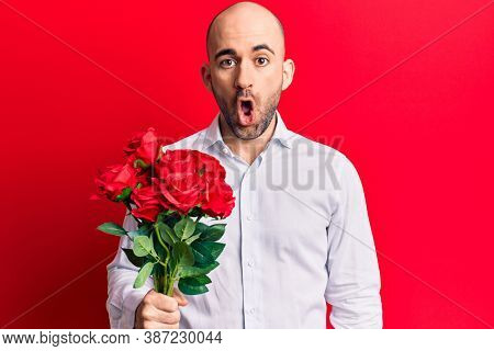 Young handsome bald man holding bouquet of red flowers scared and amazed with open mouth for surprise, disbelief face