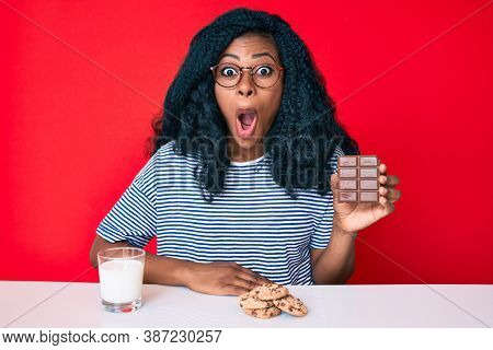 Beautiful african woman eating a chocolate bar and drinking glass of milk scared and amazed with open mouth for surprise, disbelief face