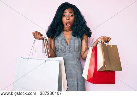 Young african american woman holding shopping bags afraid and shocked with surprise and amazed expression, fear and excited face.