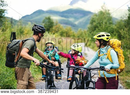 Family With Small Children Cycling Outdoors In Summer Nature, Resting.