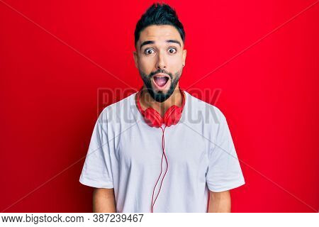 Young man with beard listening to music using headphones afraid and shocked with surprise and amazed expression, fear and excited face.