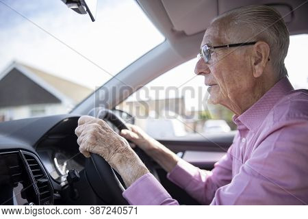 Worried Senior Male Driver Looking Through Car Windscreen