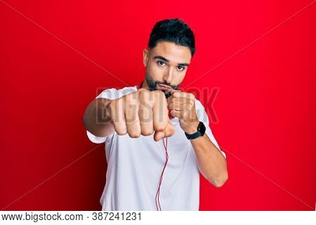 Young man with beard listening to music using headphones punching fist to fight, aggressive and angry attack, threat and violence