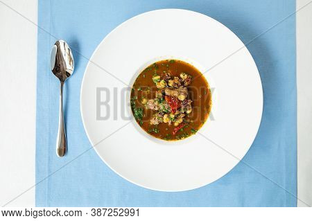 Top View On Spanish Traditional Oxtail Soup In White Plate On The Blue Table