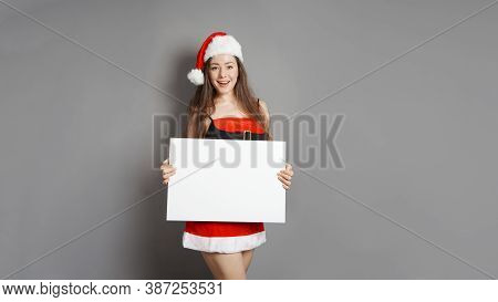 Young Woman Dressed In Santa Claus Christmas Costume Presenting Blank Sign With Copy Space
