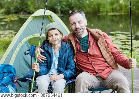 Portrait Of Happy Father Embracing Son While Enjoying Fishing Trip Together And Smiling At Camera