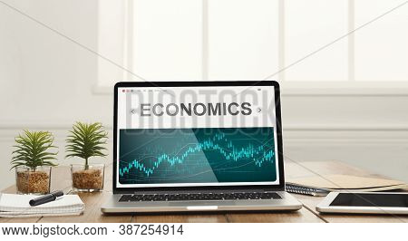 Laptop With Word Economics On Screen Standing On Office Desk. Economical Growth And Financial Busine