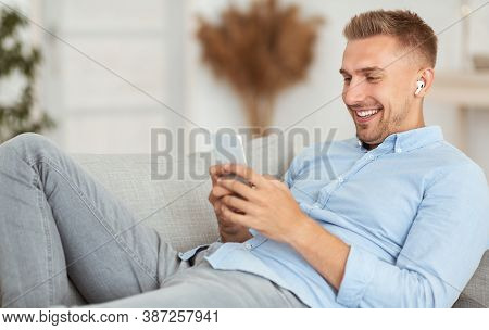 Free Time And Leisure Concept. Portrait Of Relaxed Happy Man Listening To Music In Wireless Earphone