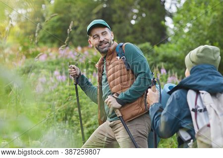 Portrait Of Happy Father And Son Hiking Together And Walking Uphill, Focus On Smiling Mature Man Wit