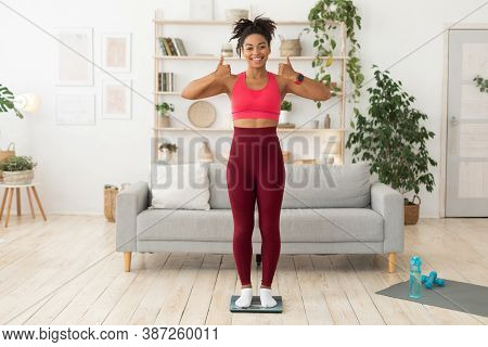 Fit Black Lady After Weight Loss Standing On Scales Gesturing Thumbs-up Approving Fitness Lifestyle