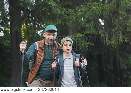Waist Up Portrait Of Happy Father And Son Hiking Together And Looking At Camera While Walking In For