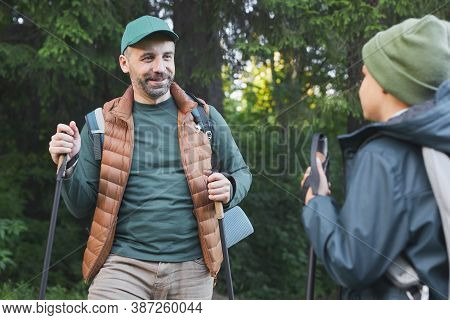 Waist Up Portrait Of Happy Father And Son Hiking Together And Talking While Walking In Forest With H