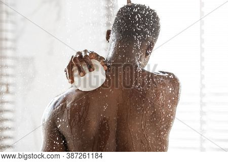 African American Man Washing Back With Sponge Taking Shower Standing Under Falling Water Drops In Mo