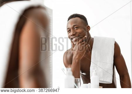 Handsome Muscular Black Man Touching Smooth Well-shaved Face Looking At His Reflection In Mirror Sta