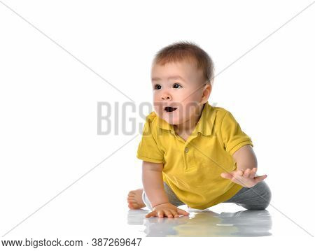 Curious Boy Crawling Across The White Floor Studio Shot. A Cute Cute Interested Child With An Inquis