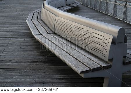 Curved Empty Wooden Benches With Metal Backrest Along River