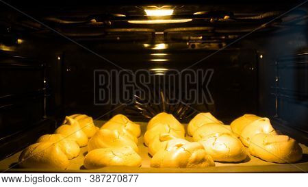 The Process Of Cooking Meringue In The Oven. The Meringues Are On A Baking Sheet.