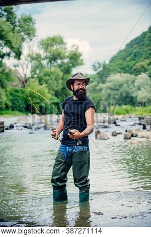 Man Fisherman Holds A Fish. Happy Cheerful People. Fishing In River. Angler Catching The Fish. Beard
