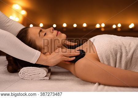 Young Woman Receiving Hot Stone Massage At Modern Spa Decorated With Candles, Side View. Spa Therapi