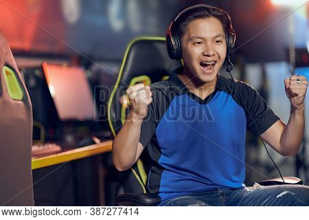 Winning. Portrait Of Excited Asian Guy, Male Cyber Sport Gamer Wearing Headphones Looking At Pc Scre