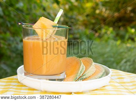 Glass Of Fresh Cantaloupe Smoothie With Mint Leaves And Striped Straw And Cantaloupe Melon Slices On