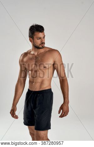 Vertical Shot Of A Young Muscular Caucasian Man Showing His Naked Torso And Looking Away While Posin