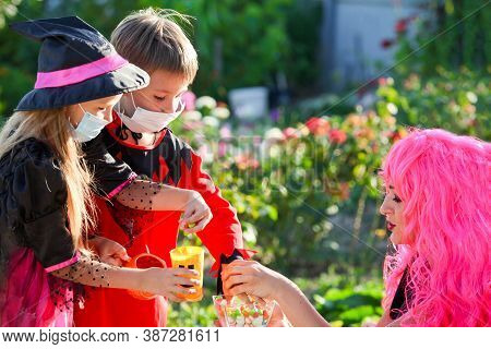 Children Trick Or Treat In Halloween Costume And Medical Mask. A Little Boy And A Girl In Suits Duri