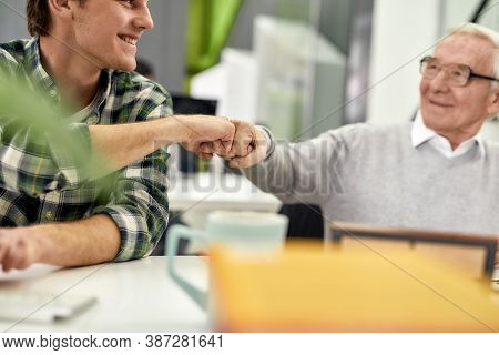 Cropped Shot Of Aged Man, Senior Intern Smiling At His Young Colleague And Doing A Fist Bump, Friend
