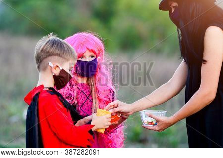 Children Trick Or Treat In Halloween Costume And Medical Mask. A Boy And A Girl In Suits During The