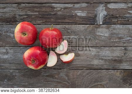 Three Whole Red Apples And Apple Slices On The Wooden Background. Autumn Mood. Organic And Healthy F