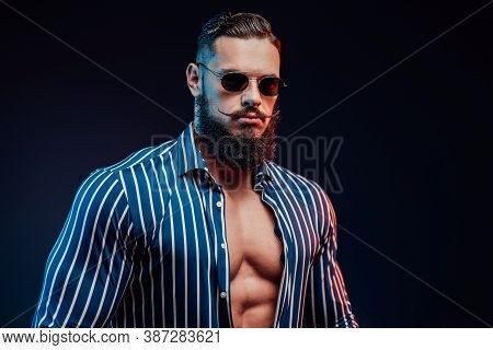 Masculine And Sportive Gentleman In Sunglasses With Black Beard And Mustache Posing In Dark Backgrou