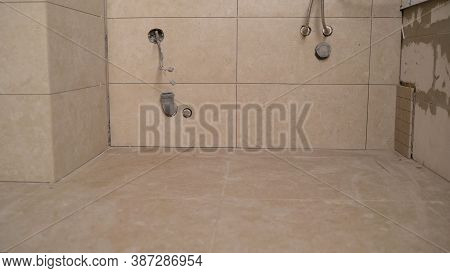 Laying Tiles In The Bathroom. Man Tiling A Wall In The Bathroom. Ceramic Tiles. Tiler Placing Cerami