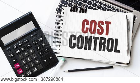 Keyboard Of Laptop, Calcualtor, Pencil And Notepad With Text Cost Control On The White Background