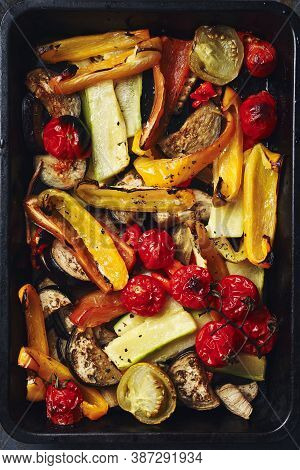 Roasted Sliced Vegetables On A Baking Tray. Oven-baked Tomatoes, Eggplants, Zucchini, Bell Peppers.
