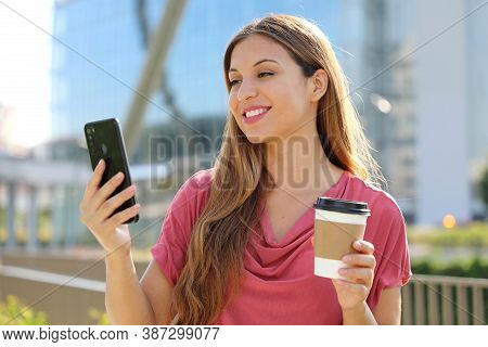 Smiling Young Brazilian Woman Wearing Pink Blouse Video Calling With Smartphone Outdoors, Holding Ta