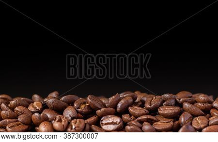 Coffee Beans On A Black Background. Heap Of Coffee Beans. Poured Coffee Close-up