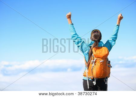 Winner / Success concept. Hiker woman cheering elated and blissful with arms raised in the sky after hiking to mountain top summit above the clouds.