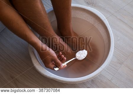 Man Put Spoon Of Baking Soda In Bath With Hot Water For His Feet. Homemade Bath Soak For Dry Feet Sk