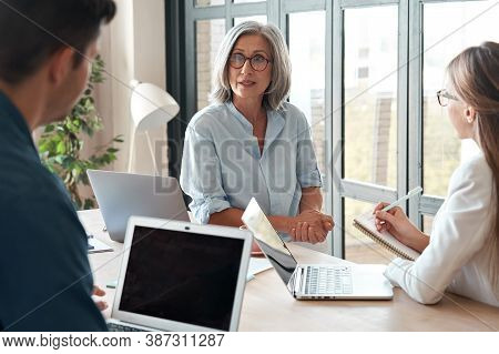 Mature Old Female Mentor Coach Supervisor Training Young Interns At Group Office Meeting Professiona