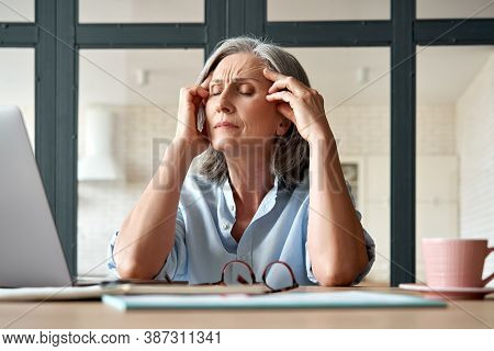 Tired Stressed Old Mature Business Woman Suffering From Headache At Work. Upset Sick Senior Middle A