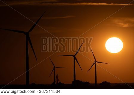 Sun Setting Behind A Group Of Wind Turbines