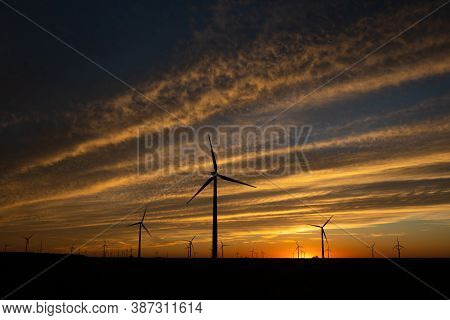 Sunset Behind A Field Of Wind Turbines