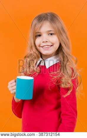 Girl With Long Blond Hair In Red Sweater Hold Mug. Child Smile With Blue Cup On Orange Background. T
