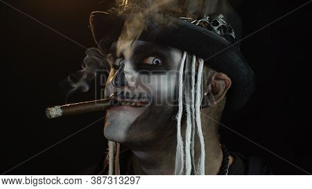 Creepy Man With Skeleton Makeup In Top-hat With Feathers. Guy Smoking Cigar, Making Faces, Looking A