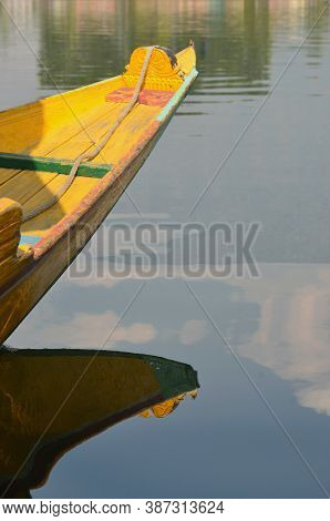 A Bright Yellow Prow Of A Wooden Boat Has Blue And Green Trim. It Is Reflected In The Still Waters O